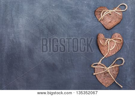 Three (3) decorative hearts made from tree bark on chalkboard, positioned on right side of the photo. Hearts decorated with eco twine. Eco decor. St. Valentines greeting card idea. Handmade design.