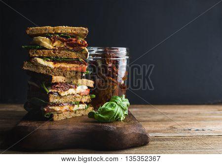 Caprese sandwich or panini. Whole grain bread, mozzarella, cherry and dried tomatoes, basil. Dark background, copy space