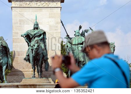 Tourist is taking picture on Heroes' Square (Budapest, Hungary)