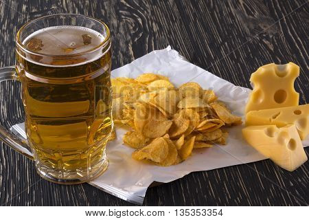 Potato chips, cheese and glass of beer on a wooden table.