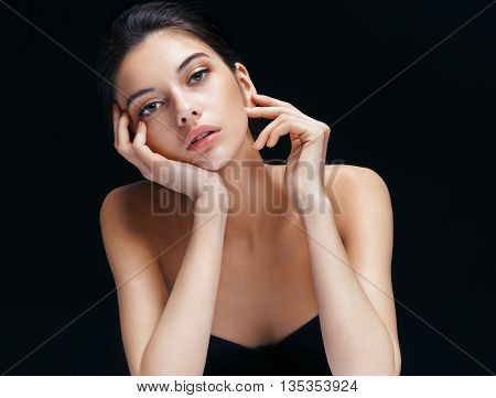Beautiful girl with perfect make up touching her face. Image with brunette woman on black background. Youth and skin care concept