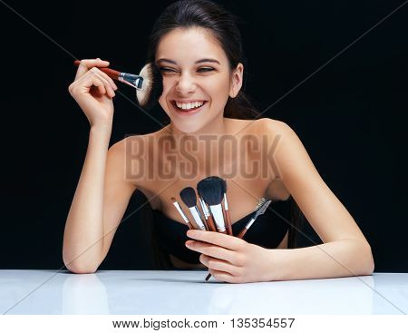Smiling brunette girl with make up brushes near her face. An attractive girl of European appearance on black background