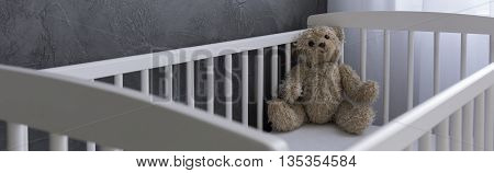 Teddy bear lying in white cot panorama