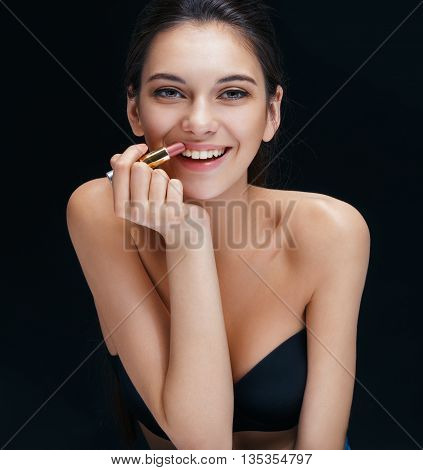 Beautiful brunette girl toothy smiling with lipstick. Close up of an attractive girl of European appearance on black background.
