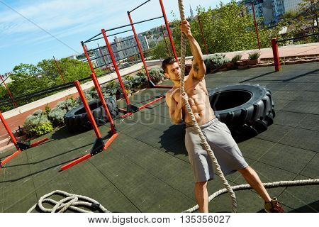 Young man doing fitness training at outdoor street fitness gym.