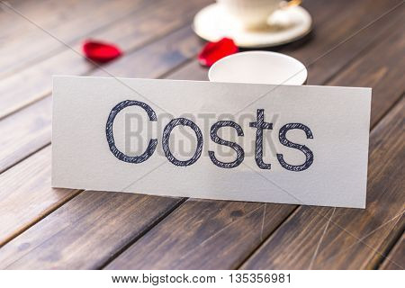 white paper with word cost against elegant coffee cup in cafe
