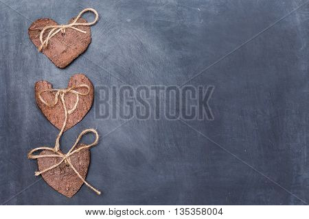 Three (3) decorative hearts made from tree bark on chalkboard, positioned on left side of the photo. Hearts decorated with eco twine. Eco decor. St. Valentines greeting card idea. Handmade design.