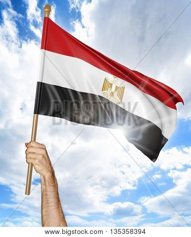 Person's hand holding the Egyptian national flag and waving it in the sky, 3D rendering
