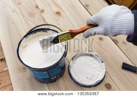 Holding painting brush in the jar with the white paint. Painting timber boards outside with the white paint or white coloured emulsion using 2 inches painting brush.