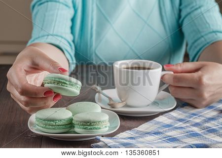 Female hands holding colorful french macaroons and cup of tea