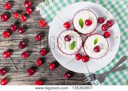 Italian dessert of cherry juice and sweetened cream thickened with gelatin and molded on a dish with cherries on a dark wooden background view from above