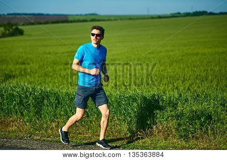 man runner athlete jogging along a green field in the early morning. man fitness sunset jogging workout wellness concept. free space in front of the person
