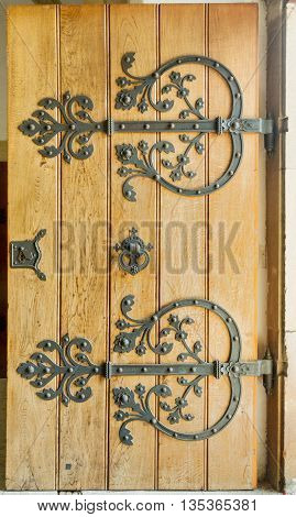 Large wooden door with a handle wrought iron handle.