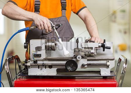 Machinist working a metal lathe in workroom