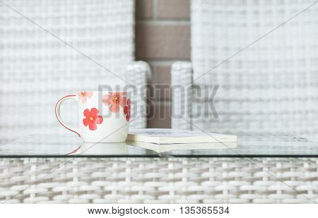 Closeup cute cup on blurred book and wood weave table and chair textured background