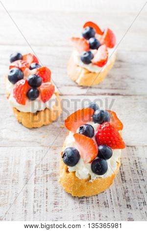 Small canape, crostini with grilled baguette with cream cheese, blueberry, strawberry and mint on old white wooden background. Delicious appetizer or dessert.