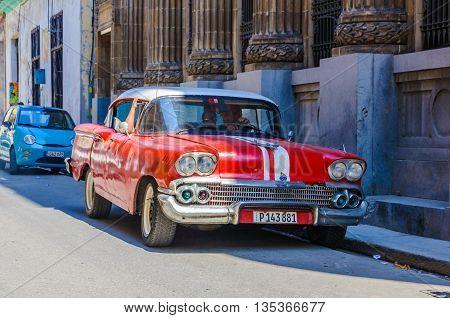 HAVANA, CUBA - MARCH 16, 2016: Old red car parked in the Old Havana neighborhood Cuba