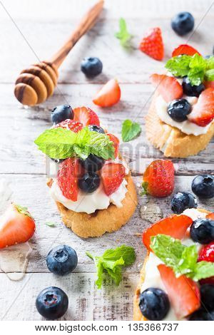 Small canape, crostini with grilled baguette with cream cheese, blueberry, strawberry, honey and mint on old white wooden background. Delicious appetizer or dessert.