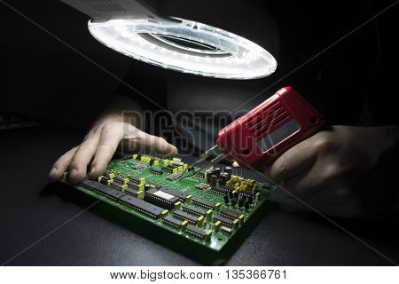 Man hands fixing computer motherboard on the black workbench