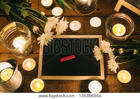 Writing in memory, red chalk on small chalkboard among candles