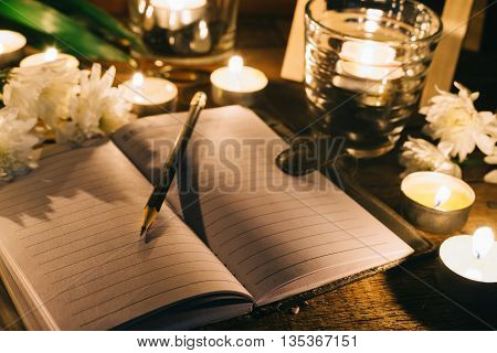 Writing in memory, pencil on empty notebook among candles