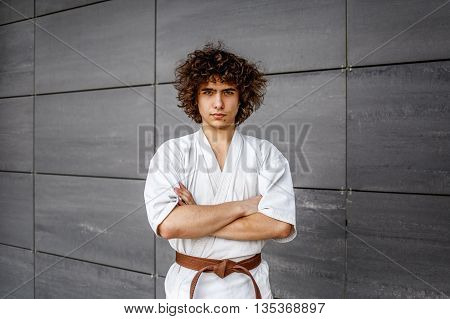 handsome young karate coach stands near the wall in a kimono