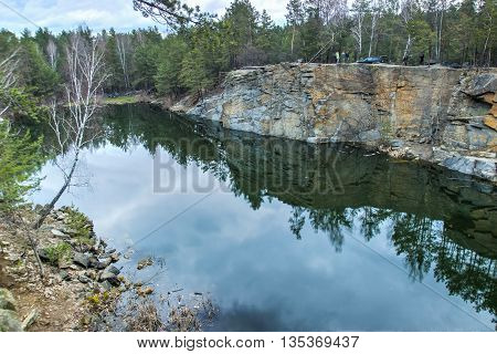Abandoned granite quarry under water at forest