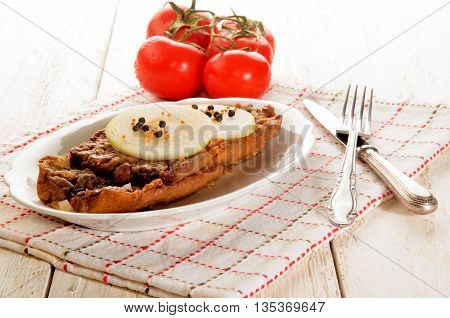 pickled herring with onion slices and peppercorns on a plate