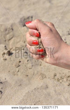 Close Up Of Female Hand Releasing Sand. Sand Flowing Through The Hands Against Sandy Beach. Summer V