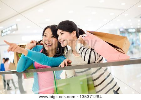 Two women holding shopping bag and looking for another shop