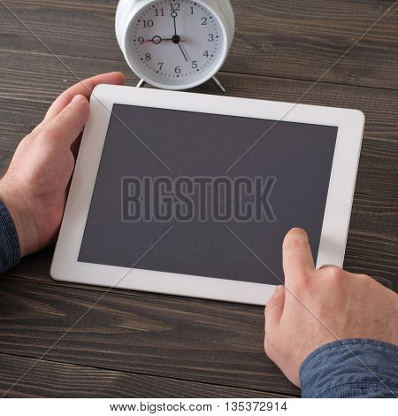 Man clicks on the tablet screen where you can place your text sitting at the table dark wooden table in the morning