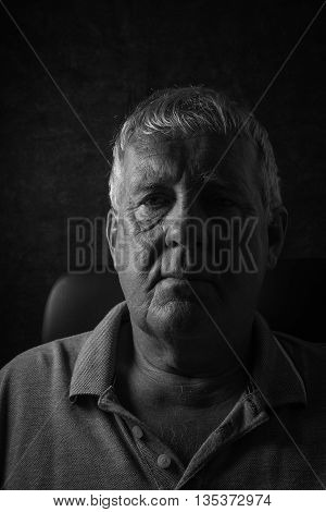 Older depressed man, selective focus on a black background