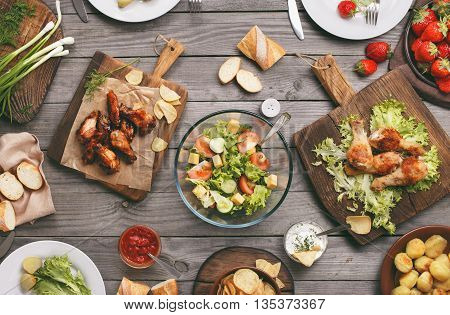 Different food cooked on the grill on a wooden table grilled chicken legs buffalo wings salad potatoes and strawberry top view. Outdoors Food Concept