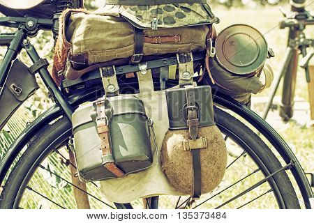 Close up photo of old military bicycle with equipment. Backpack and containers for food and drink. Vintage scene. Retro photo filter. Equipment of german soldier in World War II.