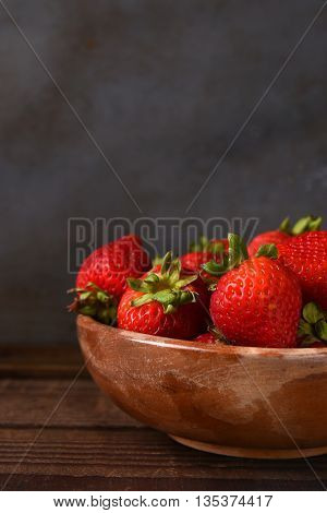Still life of a bowl full of fresh picked strawberries on a wood table. Vertical format with copy space.