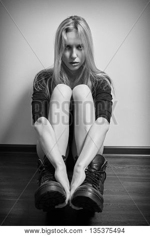 blond girl in black bodysuit and male boots sitting on floor monochrome image