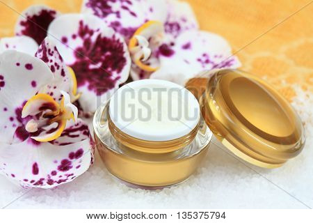 Face and body cream decorated with orchid sea salt in front