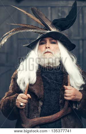 Druid old man with long grey hair beard in hunter hat with bird feathers and fur coat with deer antlers in hands on dark background