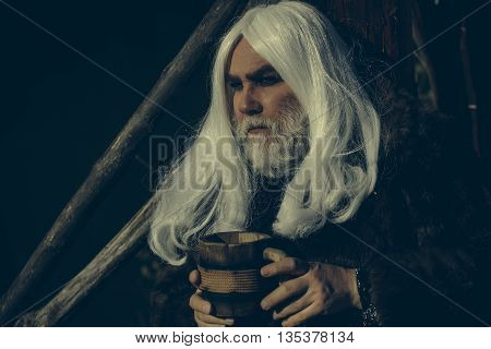 Druid old man with long grey hair and beard in fur coat with wooden mug in hands on dark background