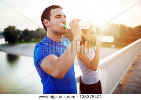 Beautiful couple staying hydrated after workout running