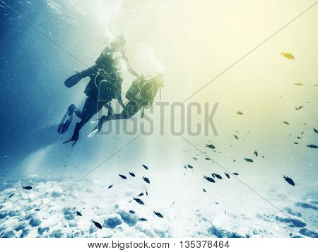 Three scuba divers. Swimming with fishes. Vintage effect.