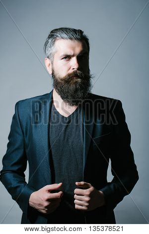 Handsome young man with long beard and moustache in black jacket in studio on grey background