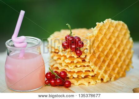 Belgian waffles with fresh berries on cutting board on background of green bokeh. grapefruit juice. pink cocktail with a straw.