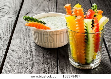 Colorful slices of raw vegetables in glasses (carrots celery cucumber sweet pepper) and yogurt sauce. The concept of diet healthy and vegetarian food. Selective focus