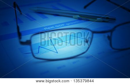 Glasses and pen on blue financial chart and graph blue tone success concept