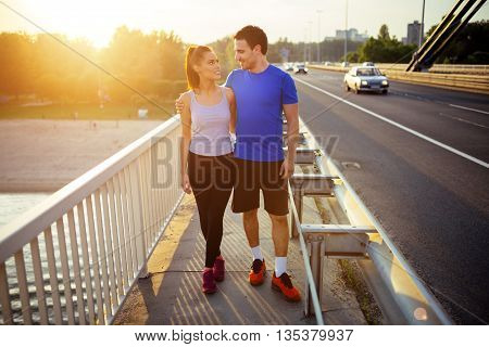 Beautiful couple bonding during mutual exercise on city bridge