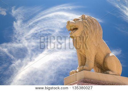 Carved sandstone lion on blue sky backgroung