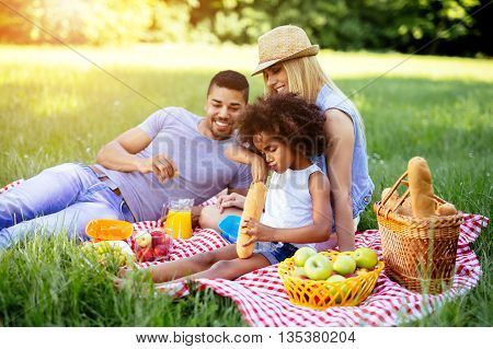 Family enjoying picnicking and food in nature outdoor