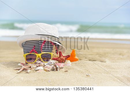 Sunglasses and a hat on a background of sea shells on.