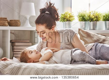 Happy loving family. Mother and her daughter child girl playing together.